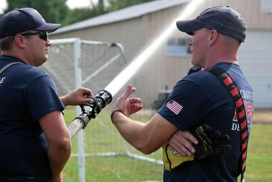 Jacksonville Fire Department Lt. Dan Klendworth (right) works with firefighter Dan Herter on proper hose handling Monday at Community Park. Photo: Samantha McDaniel-Ogletree | Journal-Courier