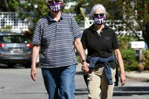 Don Schopiek (left) and his wife, Laurie, take a weekend walk in the Fort Trumbull Beach area of Milford wearing their VOTE face masks on September 12, 2020.