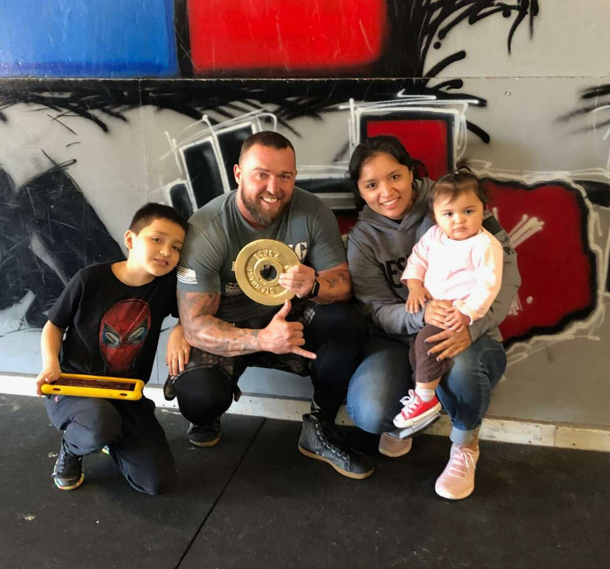Brody Clapp and his wife Priscilla, their two children, Tristan, 10, and Taya, 1, are seen in this undated photo. Brody Clapp is holding a CrossFit championship award.
