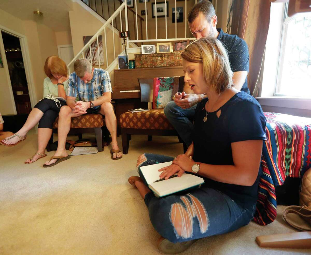 Chelley Weaver, right, prays during a service for members of Little Flock Church gather at pastor Justin Ulmer's home, Sunday, Sept. 13, 2020, in The Woodlands. Ulmer, a former student pastor, helps guide four separate meetings and plans to move to south Conroe soon.