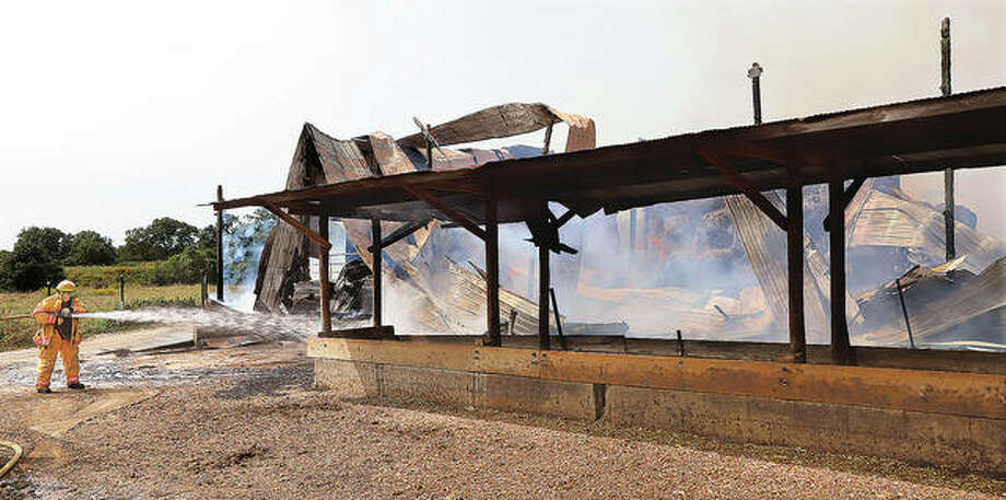A shed on a farm at 7699 Green Hedge Road — a rural Edwardsville address but in the Hamel Fire Protection District — was destroyed Monday morning by fire. The shed appeared to contain mostly hay bales but was reported to have had a grain truck inside. Firefighters from Hamel, Holiday Shores, Prairietown and Alhambra were among the departments that battled the fire for hours. At the peak of the fire, before most of the structure was burned away, smoke from the fire could be seen from as far away as Gordon Moore Park in Alton. Photo: John Badman | Hearst Newspapers
