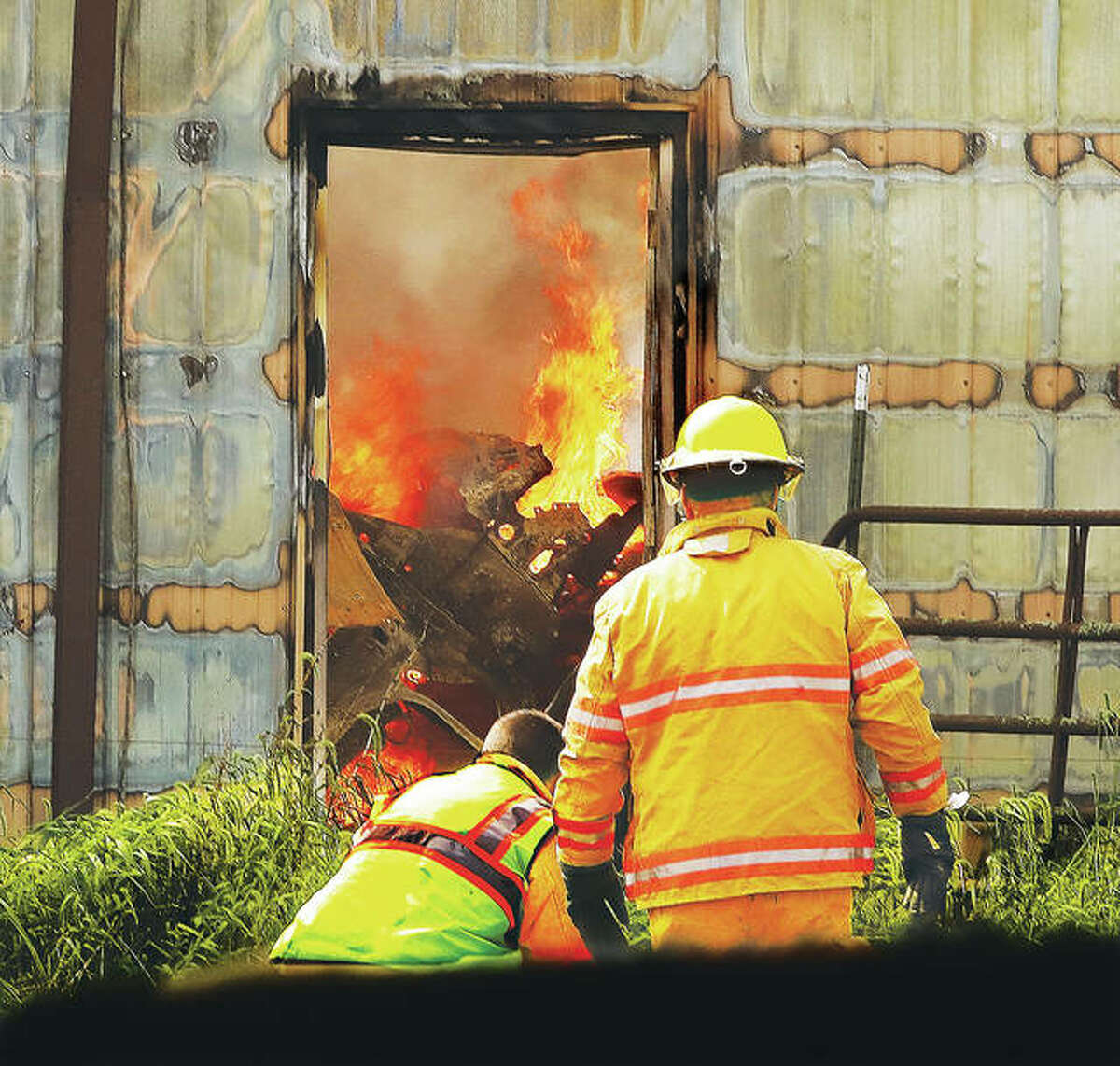 A portion of the north wall of the large shed was still standing and flames could be seen through a door consuming the interior contents Monday as firefighters worked to set up another hose line.