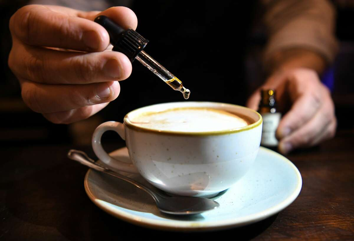 Nico Schack dribbles CBD oil into a cappuccino at the CBD Café