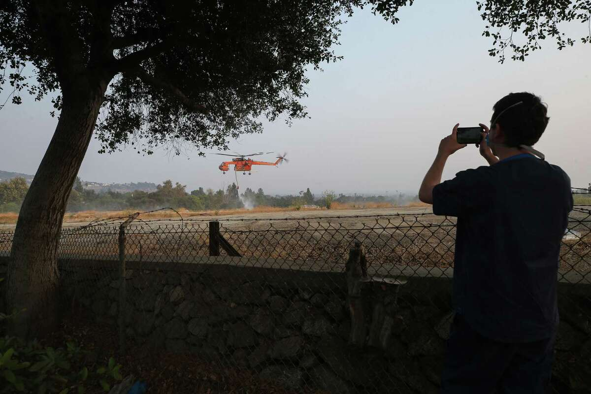 A man takes photos as a firefighting helicopter picks up water while working to extinguish the Bobcat Fire on Sept. 14, 2020, in Sierra Madre, Calif.