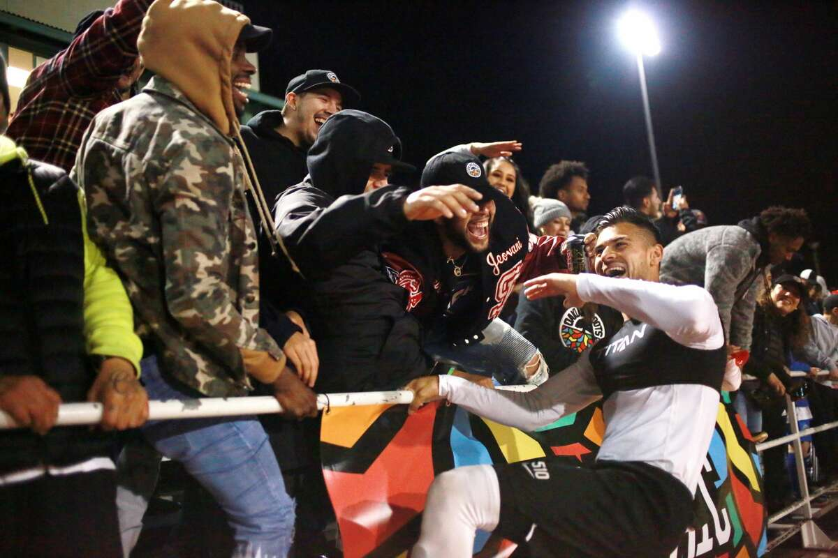 Oakland Roots fans celebrate with the Roots' Julio Cervantes at Laney Stadium in Oakland after the game against the Michigan Stars in March.