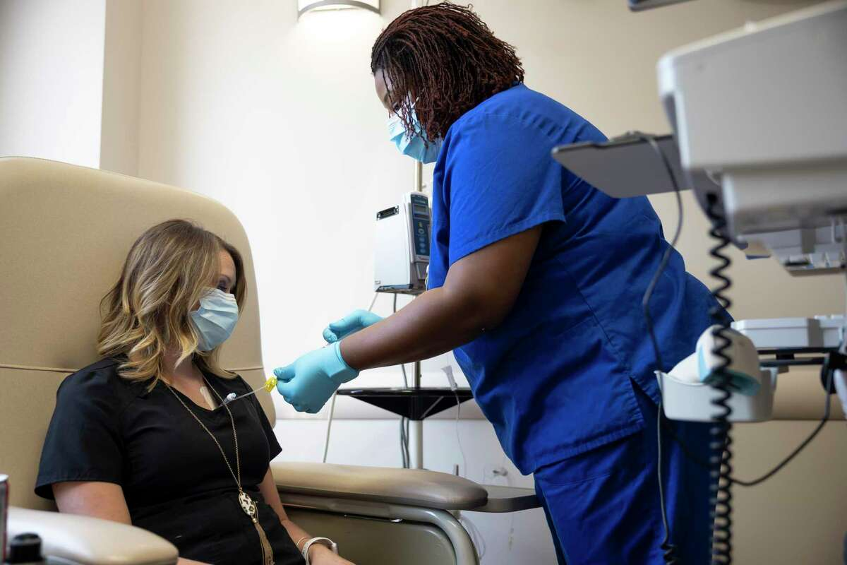 Oncology nurse Erin Jackson, right, prepares Heather Lozada's chemo infusion treatment at CHI St. Luke's Health - The Woodlands, Friday, Sept. 11, 2020. Lozada was diagnosed with Stage IV breast cancer in 2014 and it metastasized to her liver, lungs and eventually brain but is considered stable to this day.
