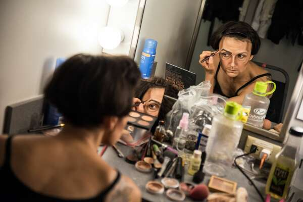 In this file photo taken on July 12, 2019 Melodie Rousseau applies makeup for her Drag King performance in Montreal, Canada. (Photo by MARTIN OUELLET-DIOTTE / AFP via Getty Images)