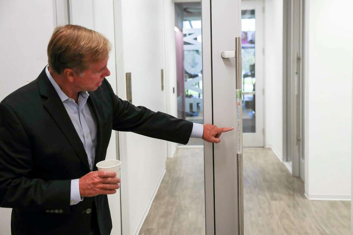 Scott Martin, executive managing director of Granite Properties, points to an anti-microbial pad on a door handle while giving a tour Wednesday, Aug. 19, 2020, at one of the company's properties in Houston.