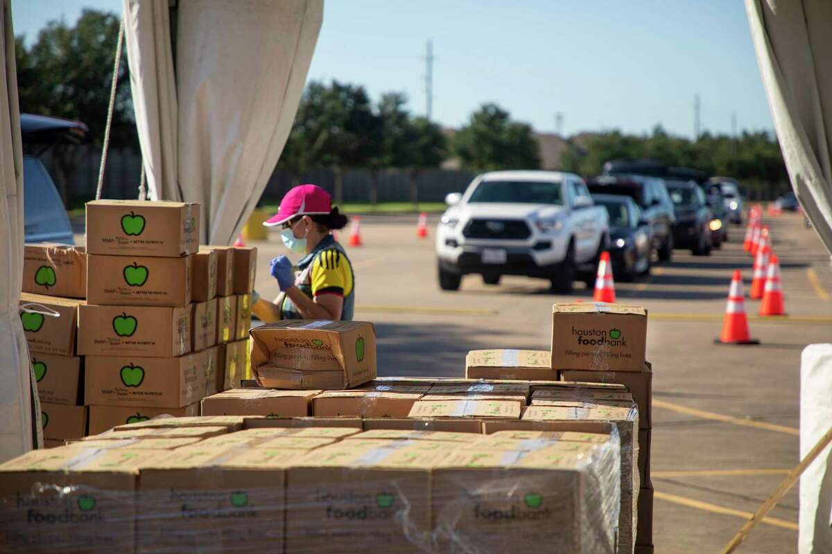 Cars line up for food boxes during a community distribution in April organized by the Houston Food Bank at Berry Center in Cypress.