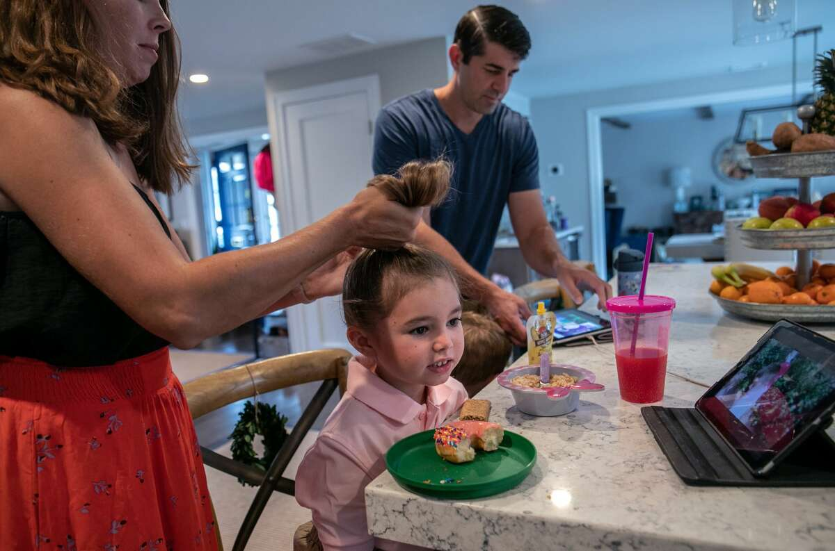 Lindsay Shea ties back her daughter Harper's hair before the first day of school on September 9, 2020 in Stamford, Connecticut.