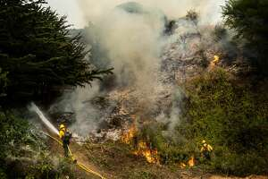 "BIG SUR, CALIFORNIA - AUGUST 22, 2020: Battling the Dolan Fire along the central California coast, Los Padres National Forest fire fighters implement a ""back-fire"" method to burn off underbrush to protect residential structures in Big Sur, California on Saturday August 22, 2020. (Photo by Melina Mara/The Washington Post via Getty Images)"