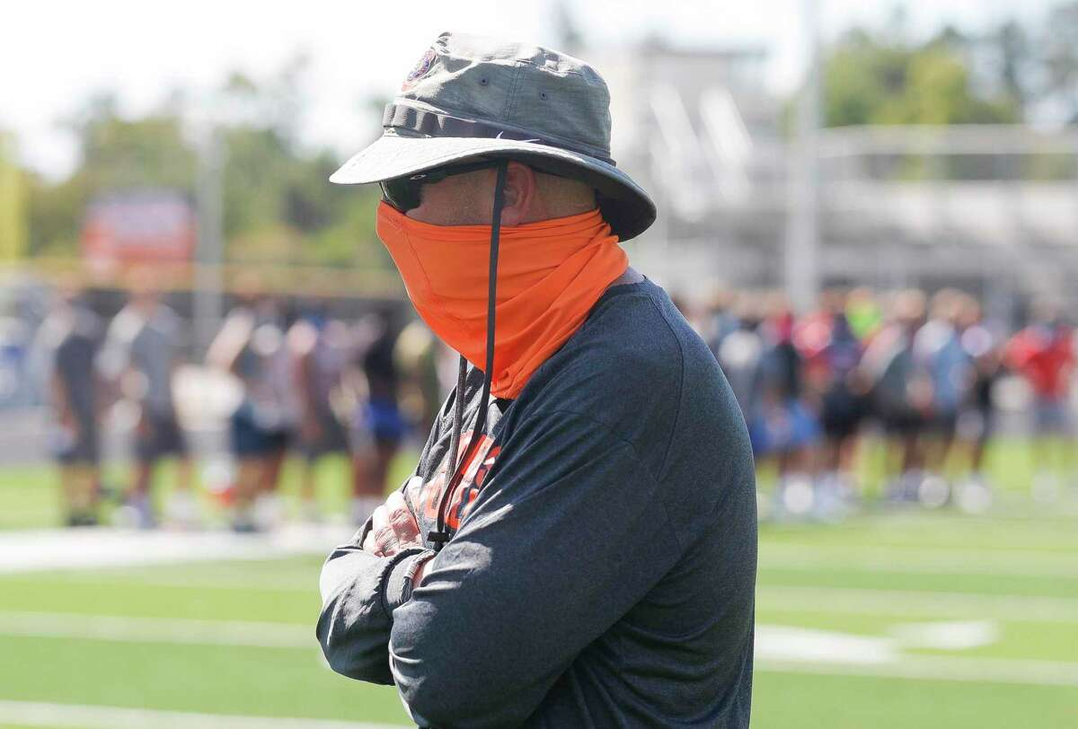 Grand Oaks head coach Mike Jackson watches a football workout as part of allowed sports-specific training at Grand Oaks High School, Wednesday, Aug. 19, 2020, in Spring.