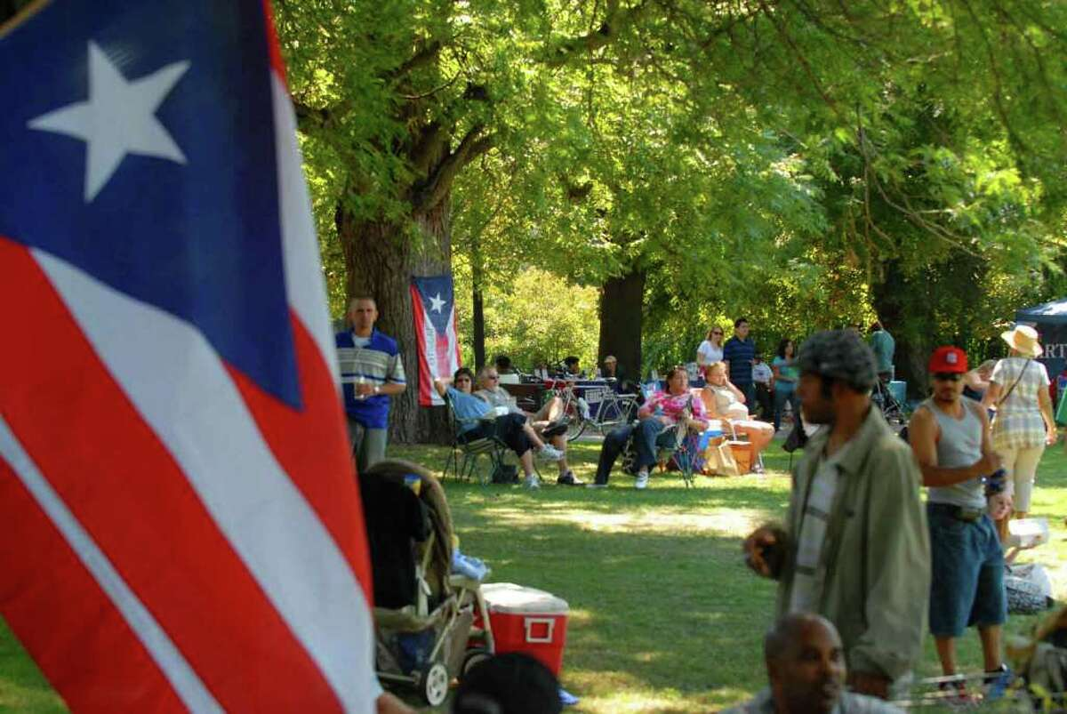 People listen to the sounds of Latin music while picnicking in the shade during the 15th Annual Latin Fest at Washington Park in Albany Saturday, Aug. 28, 2010. (Michael P. Farrell / Times Unio )