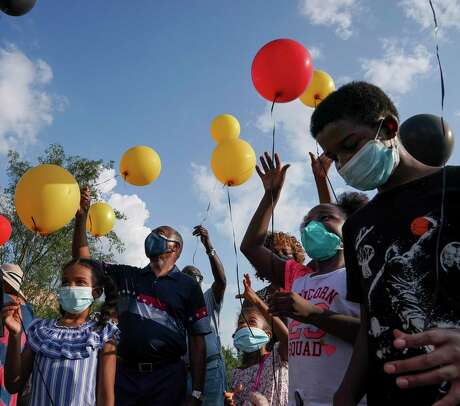 Children release balloons during the dedication ceremony of the Black Lives Matter mural painted on Carver Road, next to Carver High School, on Saturday, Sept. 12, 2020, in Houston.