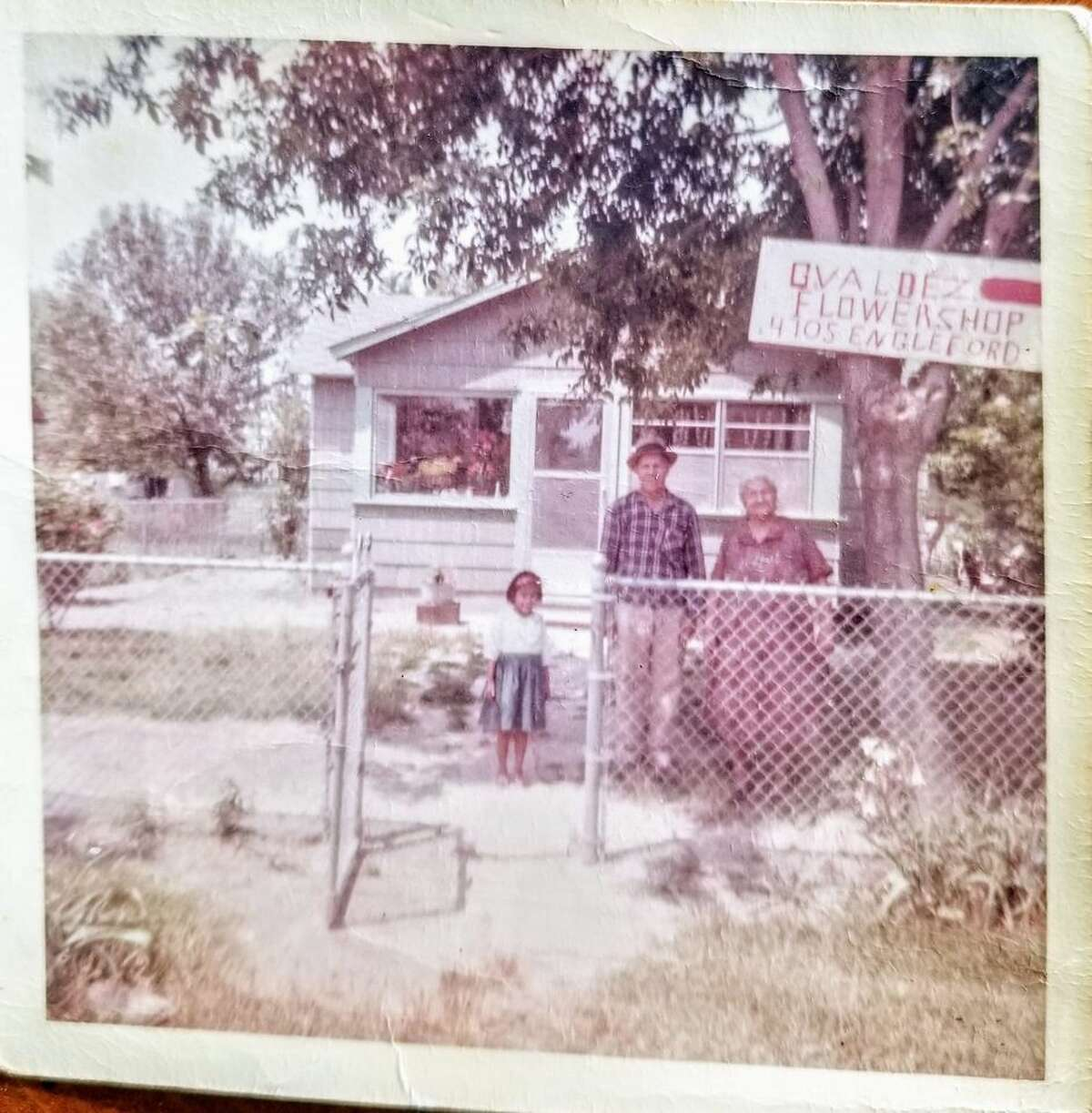 The writer's grandparents standing in front of their home promoting their flower business around the mid to late 1960s.
