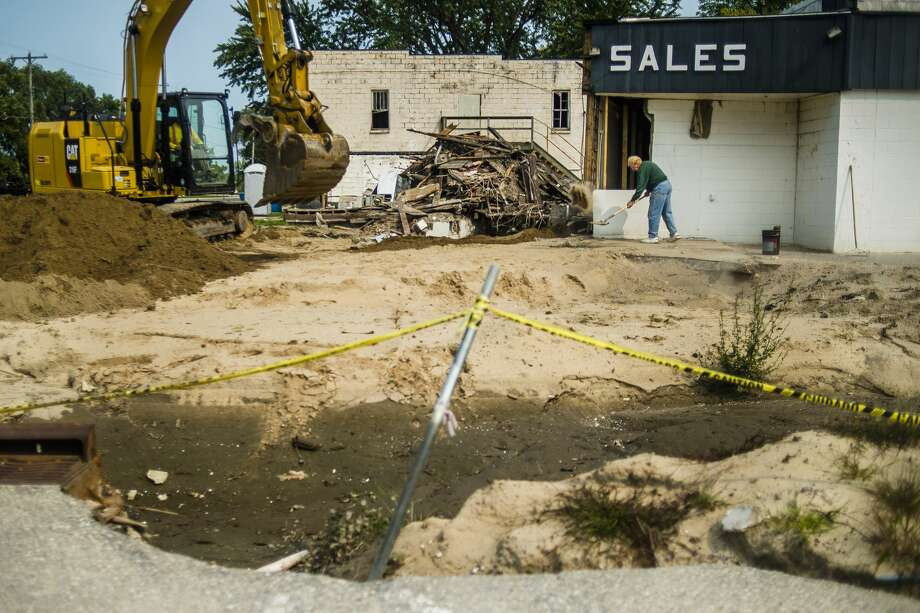 Ray Bauers, Owner of R&R Auto Sales, right, shovels debris from the front of the building as an employees of Three Rivers Corporation, left, uses an excavator to demolish the damaged structure Tuesday, Sept. 15, 2020 in downtown Sanford. Equipment was donated to Three Rivers by Fisher Contracting to assist in cleanup efforts. (Katy Kildee/kkildee@mdn.net) Photo: (Katy Kildee/kkildee@mdn.net)