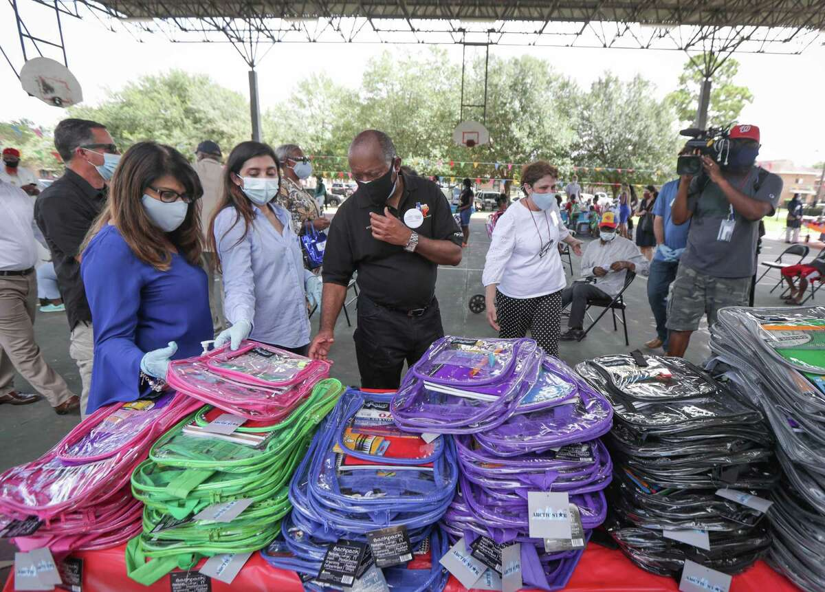 Mayor Sylvester Turner looks over backpacks during a back to school supply distribution and census awareness community event at Cuny Homes basketball court Sunday, Sept. 13, 2020, in Houston.