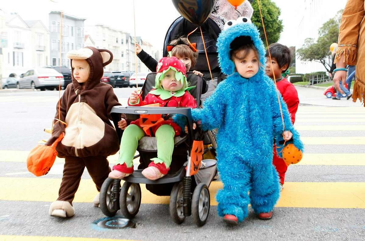 Amelie Didda, dressed as the Cookie Monster, leads her day care group to a Halloween parade on Chestnut Street.