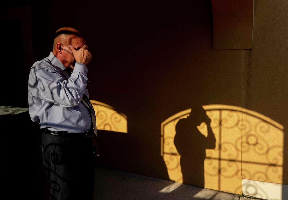 """Mortician Jeff Sonka takes a cigarette break before beginning the fourth embalmment of his workday at Compean Funeral Home on Tuesday, Aug. 4, 2020, in Houston. Sonka has been a mortician for 30 years and has seen his workload at the funeral home double since the pandemic began. """"Every once in a while it's nice to get out even if it's just for a smoke,"""" he said. """"To regroup."""""""