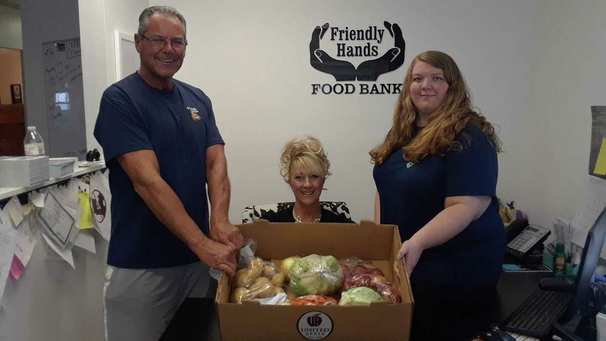 From left, Friendly Hands Food Bank board chairman Danny XXX, executive director Karen Thomas, and Abbey XXX, show a box of produce from the food bank. Friendly Hands has survived the pandemic - and increased the number of clients it serves - thanks to faithful donors, the Farms to Families fresh food program, and a