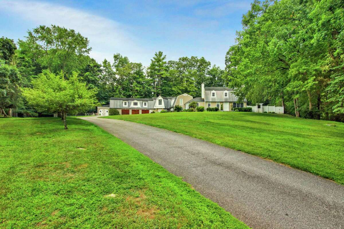 The taupe-colored colonial farmhouse at 61 River Road in the Lower Weston neighborhood sits on a 1.83-acre former equestrian estate. Also found in this backyard are fruit trees and a hot tub, and there is room for an in-ground swimming pool. Until or unless the next owners install a pool, aquatic recreation will have to take the form of fishing, which is possible directly across the street Keene Park where there is access to the Saugatuck River. The park also has a playground. Ample parking for family and guests is available in the driveway comprising pavement, cobblestones and crushed stone circles in front of the attached three-car garage. Inside, the formal living room is large enough to accommodate a grand piano in addition to the sitting area. The formal dining room is equally spacious. It has chair railing and wide-planked hardwood flooring.