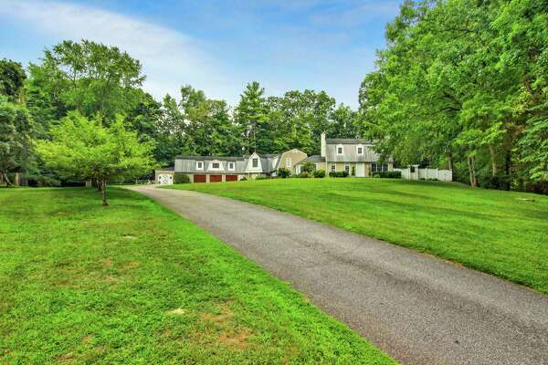 The taupe-colored colonial farmhouse at 61 River Road in the Lower Weston neighborhood sits on a 1.83-acre former equestrian estate.