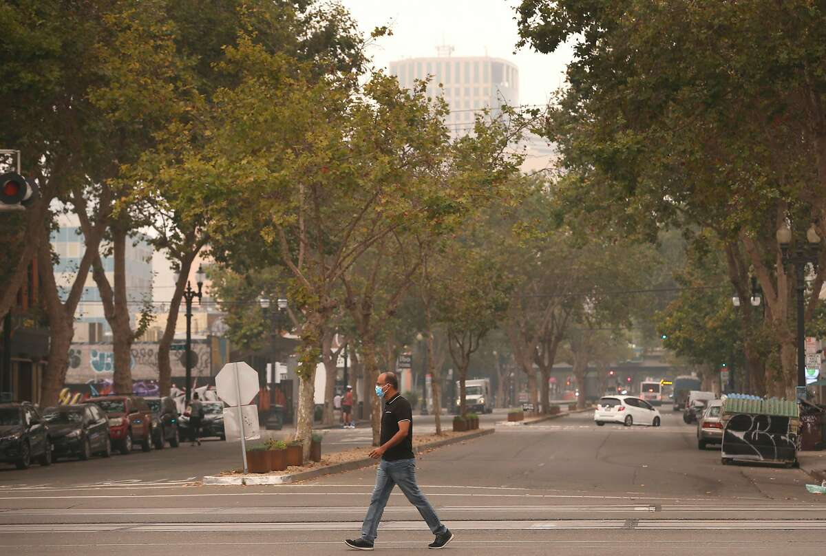 A man crosses Broadway at Embarcadero in Oakland, Calif. on Thursday, Sept. 10, 2020. The orange hue is gone but smoke from wildfires burning in Northern California and the Pacific Northwest continue to foul the air quality in the region.