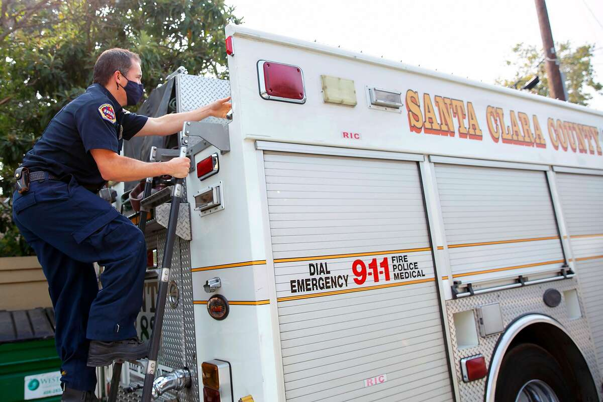 Chuck Anderson climbs up to the top of the rescue fire truck to check on gear at the start of his shift at the Los Gatos Fire Station in Los Gatos, Calif. on Saturday, September 12, 2020.
