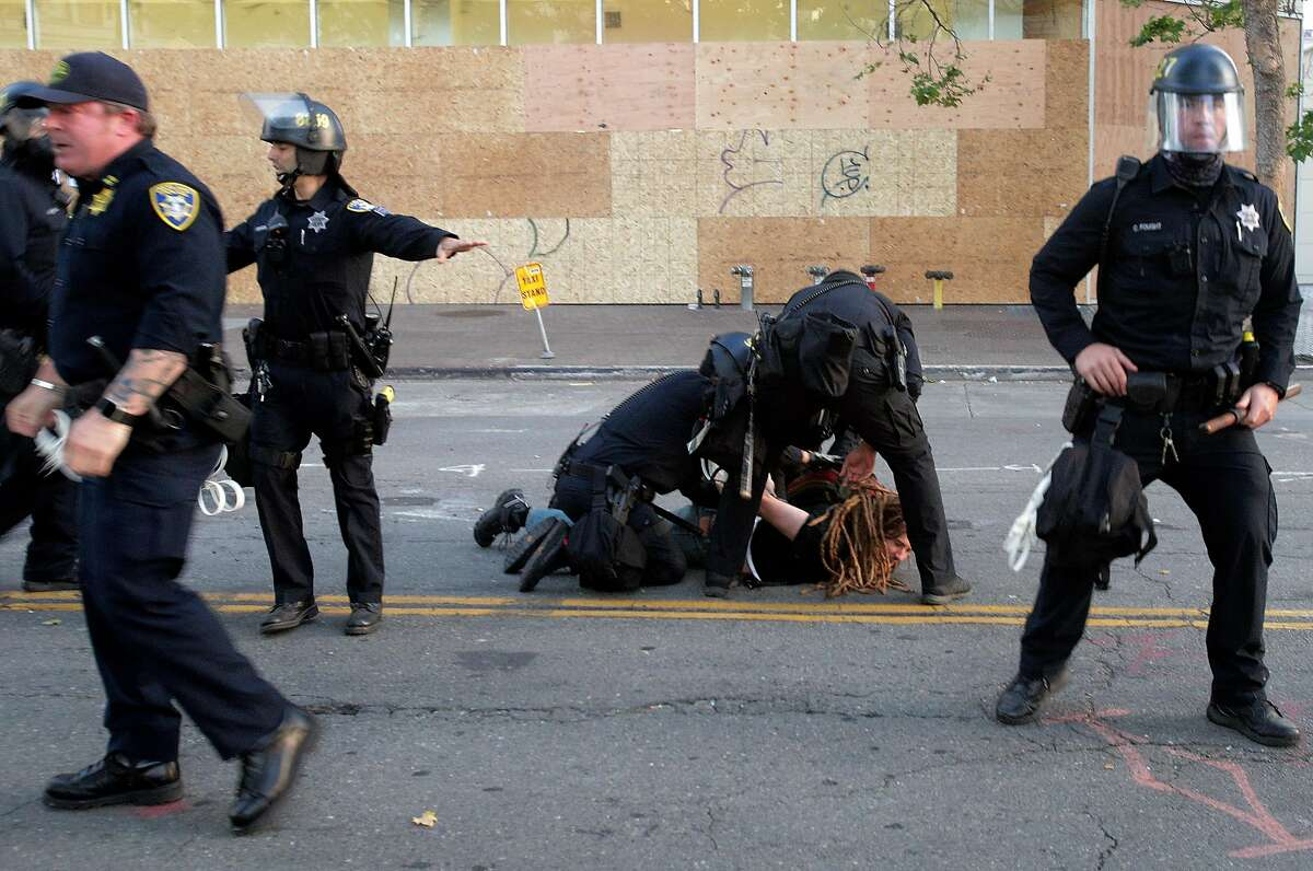 A demonstrator is arrested on the ground as officers moved in to enforce curfew to disperse a crowd that marched in a solidarity protest against police brutality and the killing of black citizens in Oakland, Calif., on Monday, June 1, 2020. Protests have erupted for days following the death of George Floyd in Minneapolis at the hands of police.