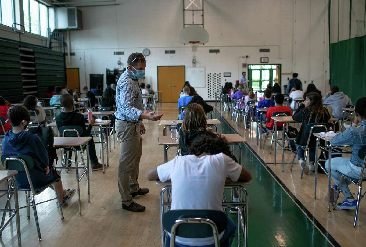 Counselor Matt Roberto monitors students during lunch period in a gymnasium at Rippowam Middle School on September 14, 2020 in Stamford, Connecticut.