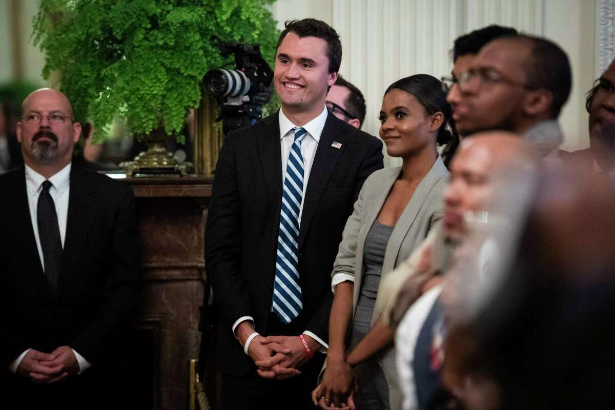 Charlie Kirk, center, and Candace Owens of Turning Point USA, listen to President Donald Trump speak in 2018.