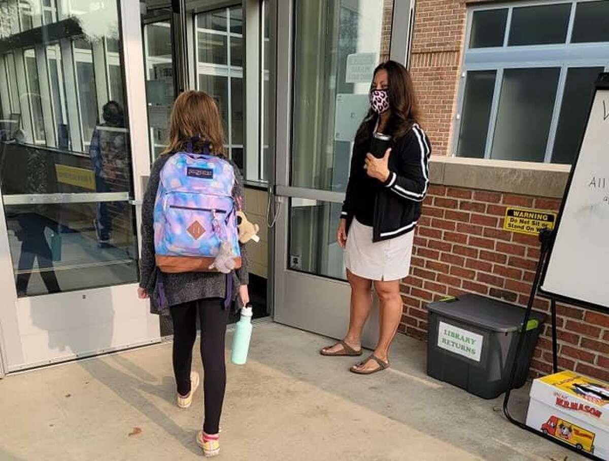Parent Jennifer Pope's daughter walks to her first day of fifth grade at Spring Glen Elementary School in Hamden.