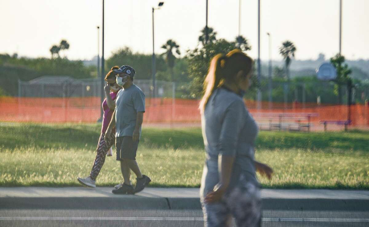 The basketball courts at Independence Hills Park remain closed, Friday, Apr. 24, 2020, as walkers exercise along the Merida Drive sidewalk.