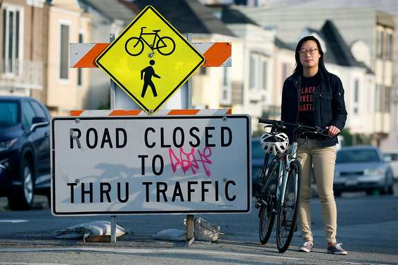 """Janice Li, with the SF Bicycle Coalition, stops at a barricade designating 41st Avenue in the Sunset district a """"slow streets"""" thoroughfare restricted to bicycles, pedestrians and local traffic only, in San Francisco, Calif. on Tuesday, Sept. 15, 2020."""