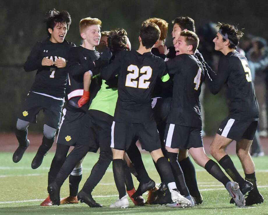 Middletown, Connecticut - Monday, November 18, 2019: The Daniel Hand H.S. soccer team mob their goalie Timothy Perez in celebration after defeating Guilford H.S. with penalty kicks during the CIAC Class L boys soccer state semifinals Monday evening at Middletown H.S. Photo: Peter Hvizdak / Hearst Connecticut Media / New Haven Register