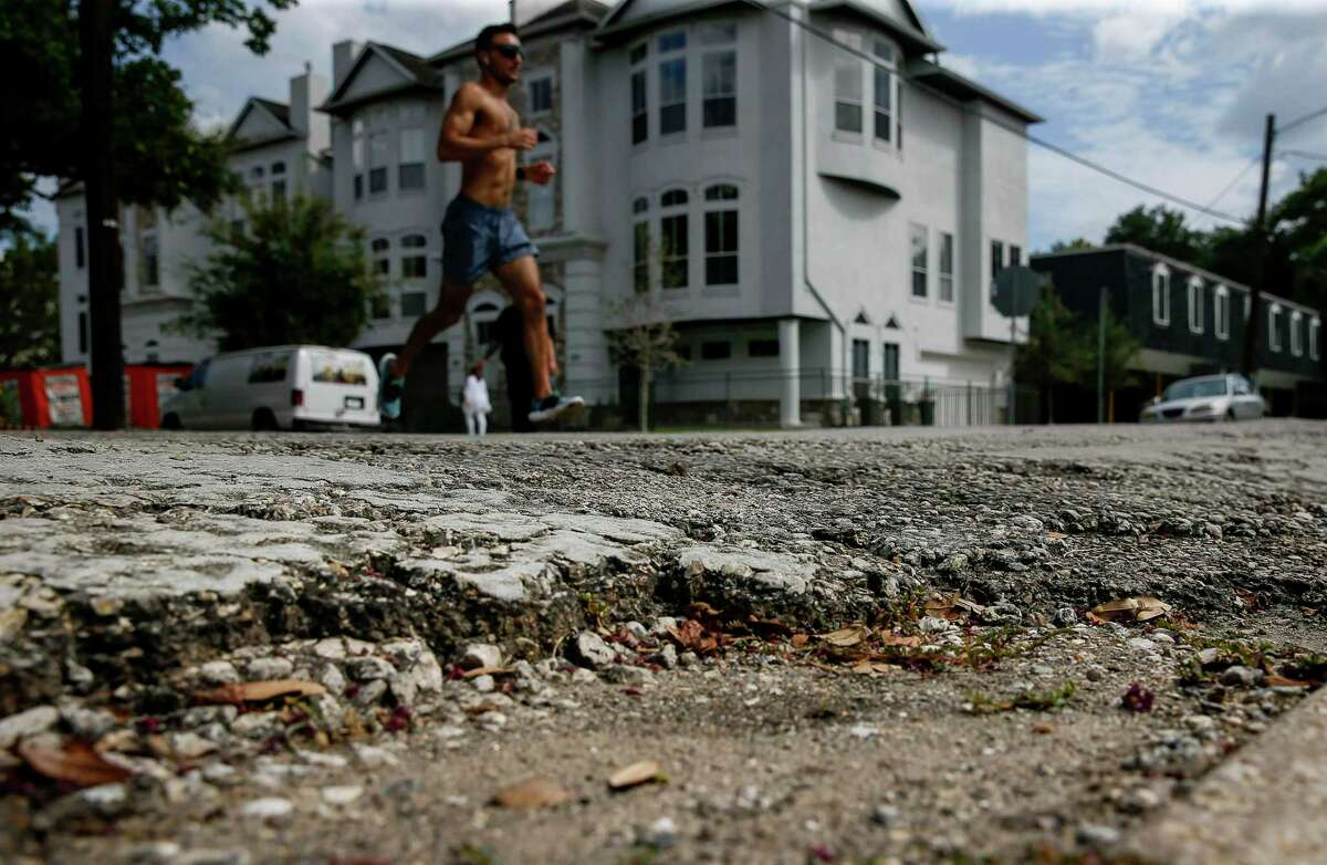 A man runs through the intersection of Kipling and Graustark on Sept. 15 2020, in Houston. City officials are preparing to revise how they maintain roads, favor more preventative maintenance to avoid costlier total rebuilds later.