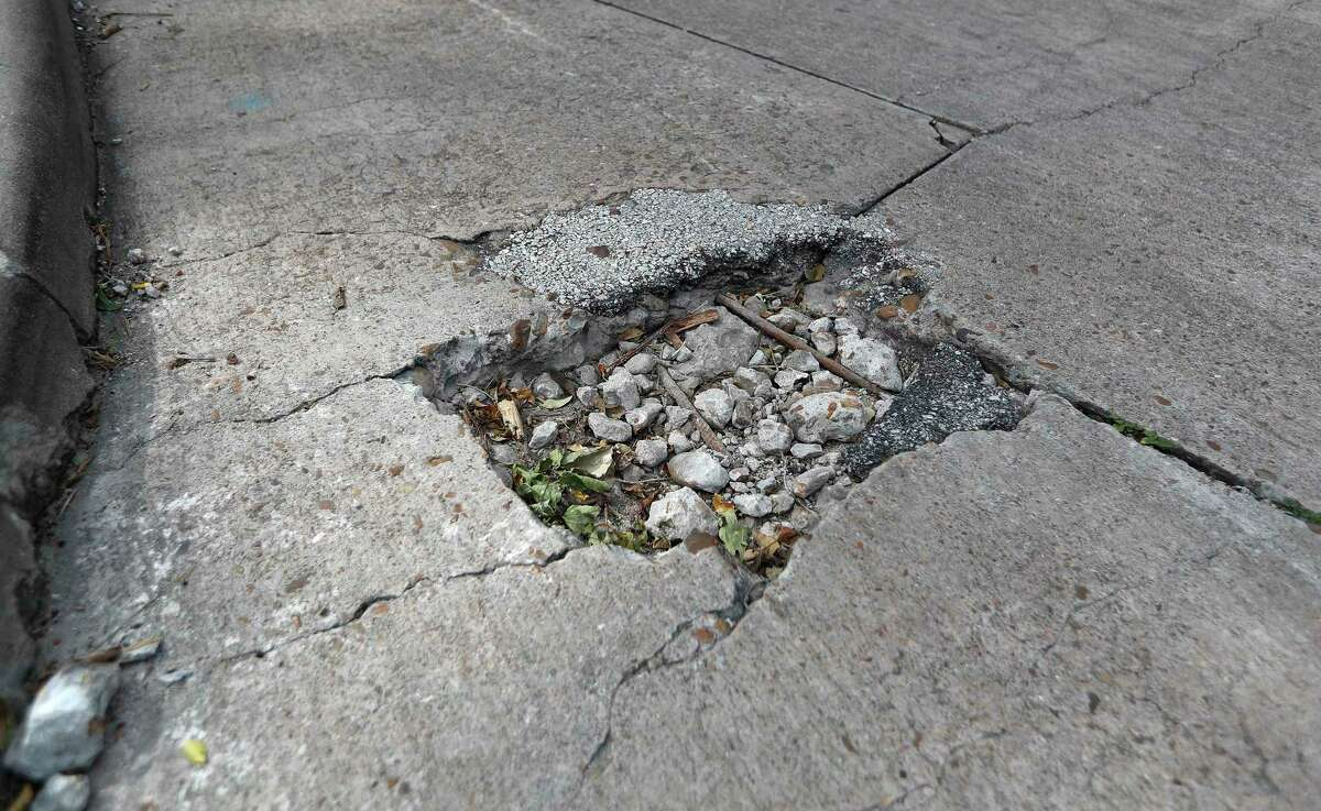 Cars pass by a hole in the street on Nance Street on Sept. 15, 2020, in Houston.