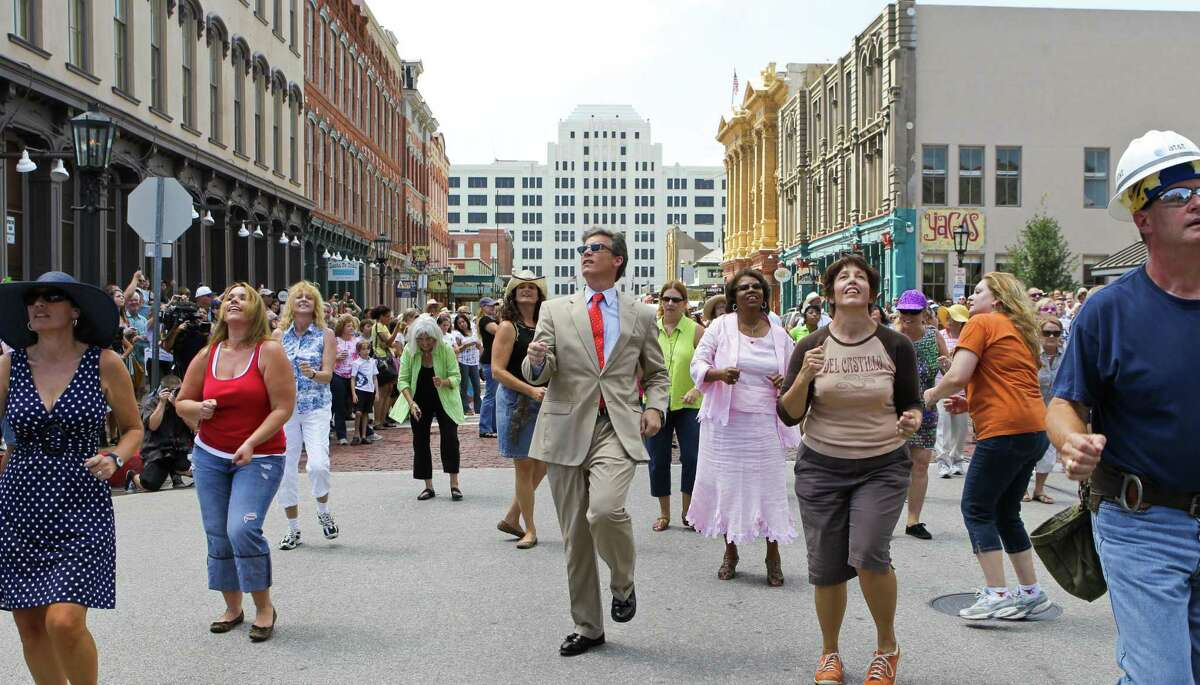 File photo shows then-Galveston Mayor Joe Jaworski, center, participating in a flash mob dance Sunday, Sept. 12, 2010, in the historic Strand district in Galveston.