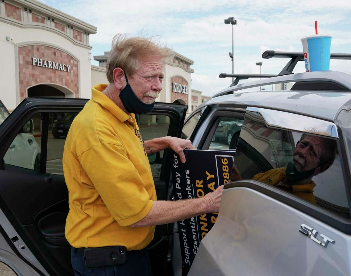 Scott Weber, grievance field director at United Food and Commercial Workers International Union Local 455, gets signs out of his vehicle before workers rallied outside a Kroger store Tuesday, Sept. 15, 2020, in Houston.