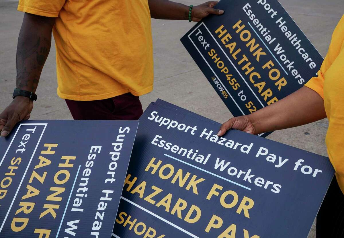 Members of the United Food and Commercial Workers International Union Local 455 get signs for a rally outside a Kroger store Tuesday, Sept. 15, 2020, in Houston.