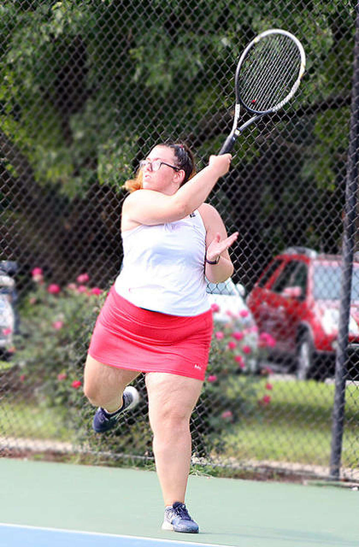 Alton's Lydia Criveau goes high to make a return in her match against Marquette's Monica Wendel Monday at the Simpson Tennis Center.