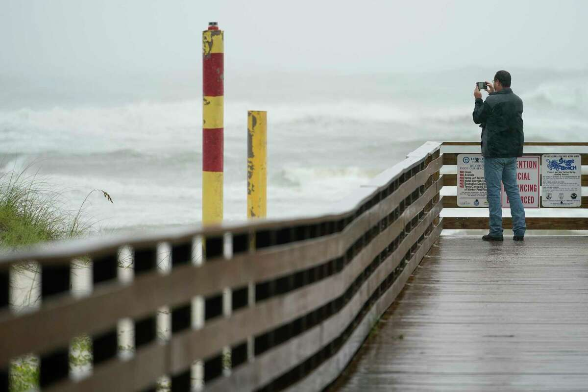 A man takes a photo on the beach at Gulf State Park, Tuesday, Sept. 15, 2020, in Gulf Shores, Ala. Hurricane Sally is crawling toward the northern Gulf Coast at just 2 mph, a pace that's enabling the storm to gather huge amounts of water to eventually dump on land. (AP Photo/Gerald Herbrt)