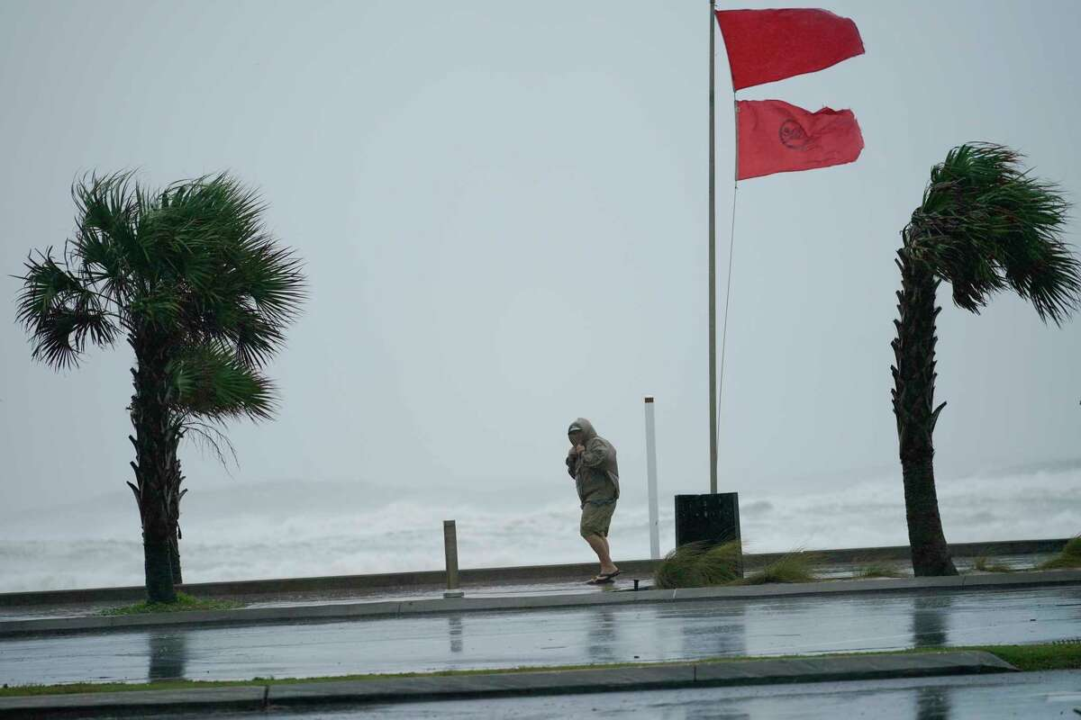 A man walks bear the gulf as Hurricane Sally moves in, Tuesday, Sept. 15, 2020, in Gulf Shores, Ala. Hurricane Sally, one of a record-tying five storms churning simultaneously in the Atlantic, closed in on the Gulf Coast on Monday with rapidly strengthening winds of at least 100 mph (161 kph) and the potential for up to 2 feet (0.6 meters) of rain that could bring severe flooding. (AP Photo/Gerald Herbrt)