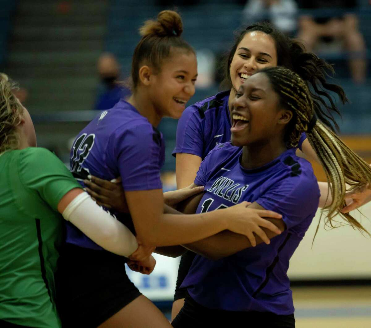 Willis freshman Secret Carroll (12) and Willis senior Keziah Smith (14) embrace one another after winning a non-district volleyball match at New Caney High School, Tuesday, Sept. 15, 2020.