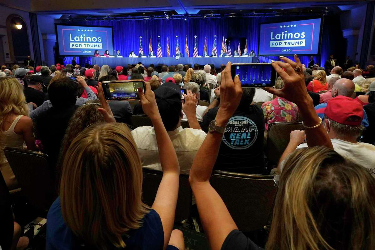 People in the crowd take pictures as President Donald Trump participates in a Latinos for Trump Coalition roundtable campaign event Monday, Sept. 14, 2020, in Phoenix. (AP Photo/Ross D. Franklin)