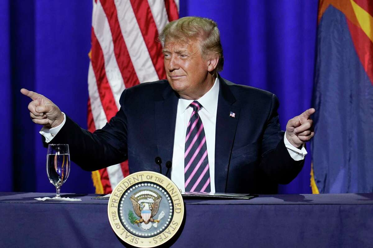 President Donald Trump points to the crowd as he arrives to participate in a Latinos for Trump Coalition roundtable Monday, Sept. 14, 2020, in Phoenix. (AP Photo/Ross D. Franklin)