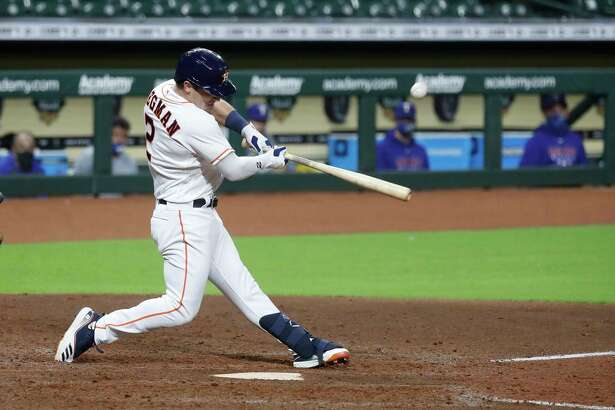 Houston Astros third baseman Alex Bregman (2) hits an RBI single scoring George Springer and Jose Altuve during the seventh inning of an MLB baseball game at Minute Maid Park, Tuesday, September 15, 2020, in Houston.