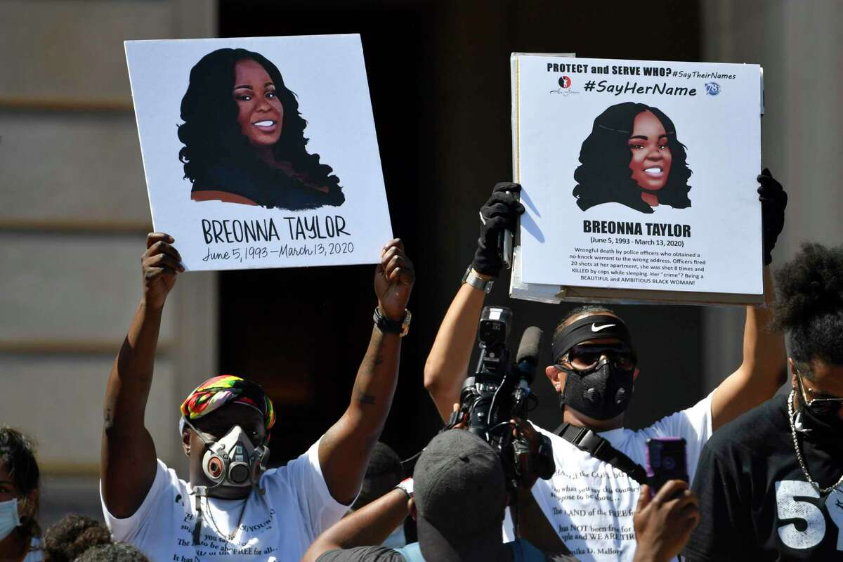 FILE - Signs are held up showing Breonna Taylor during a rally in her honor on the steps of the Kentucky State Capitol in Frankfort, Ky., Thursday, June 25, 2020. The city of Louisville will pay several million dollars to the mother of Breonna Taylor and install police reforms as part of a settlement of a lawsuit from Taylora€™s family, The Associated Press has learned. (AP Photo/Timothy D. Easley, File)