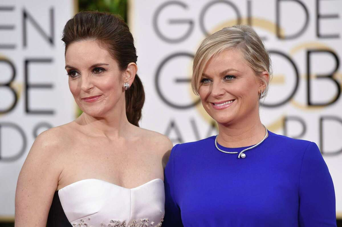 FILE - In this Jan. 11, 2015 file photo, Tina Fey, left, and Amy Poehler arrive for the 72nd annual Golden Globe Awards in Beverly Hills, Calif. On Saturday, Jan. 11, 2020, Poehler announced she and Fey will share host duties for the Golden Globes ceremony in 2021. (Photo by John Shearer/Invision/AP, File)
