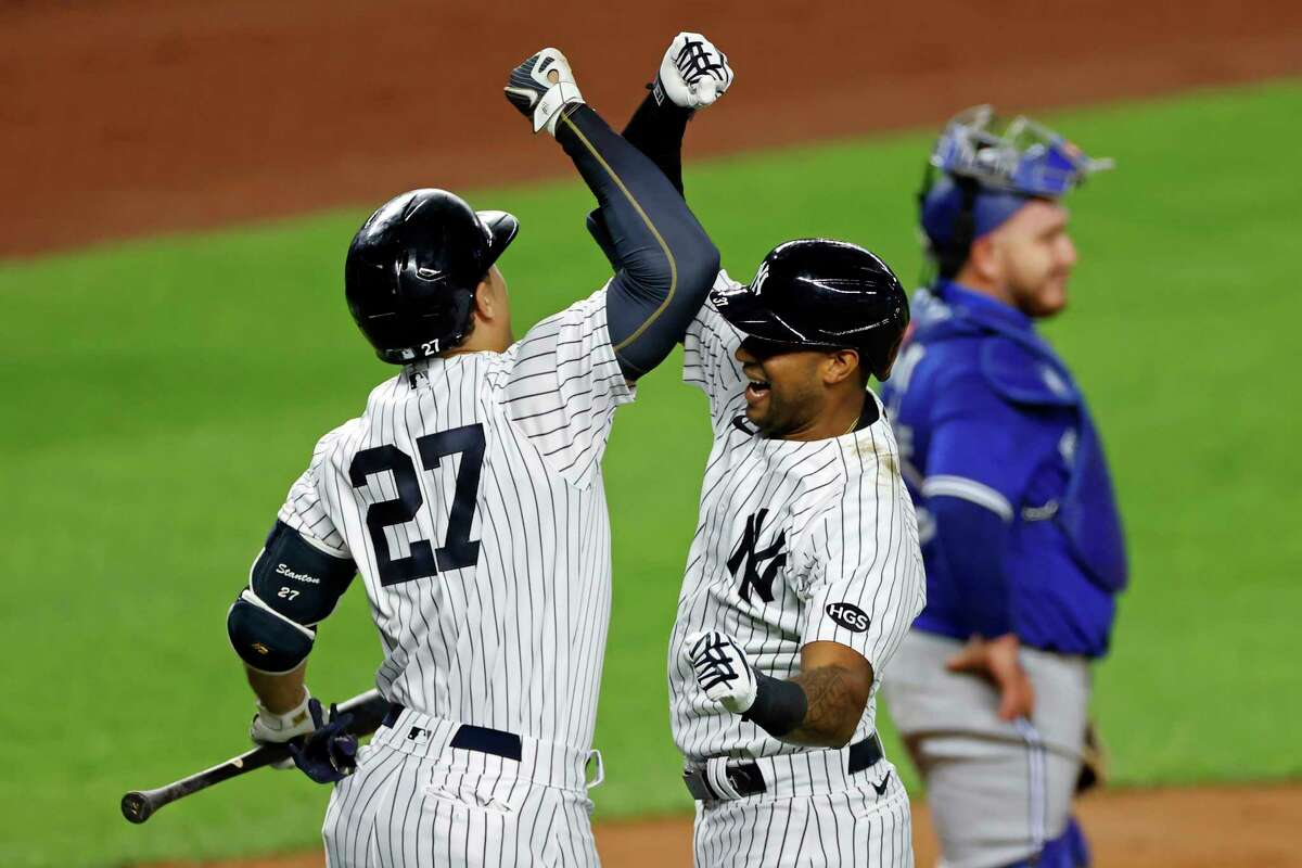 New York Yankees' Aaron Hicks celebrates hitting a solo home run with Giancarlo Stanton (27) during the second inning of a baseball game in front of Toronto Blue Jays catcher Alejandro Kirk on Tuesday, Sept. 15, 2020, in New York. (AP Photo/Adam Hunger)